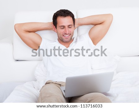 Portrait Of Young Man With Laptop, Indoors - stock photo