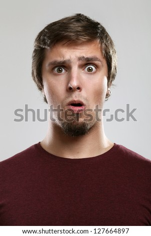 Portrait of young man with scared expression  isolated over background - stock photo