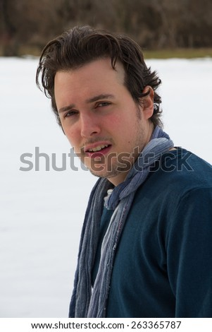 Portrait of young man with torso and face in profile looking at camera, with sweater and blue scarf around his neck and snowy background  - stock photo
