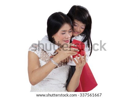 Portrait of young mother and her daughter open a gift box in the studio, isolated on white background - stock photo