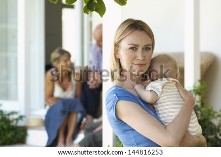 Portrait of young mother carrying baby on porch with grandparents behind - stock photo