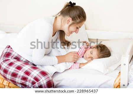 Portrait of young mother covering little sleeping girl with blanket - stock photo