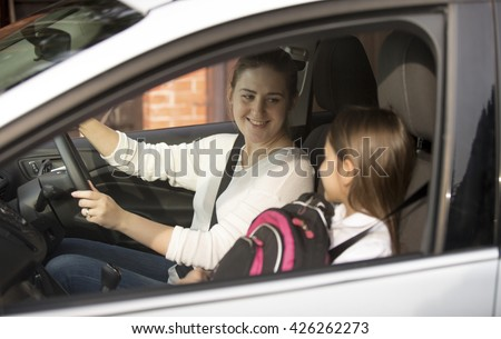 Portrait of young mother driving her daughter to school at morning - stock photo