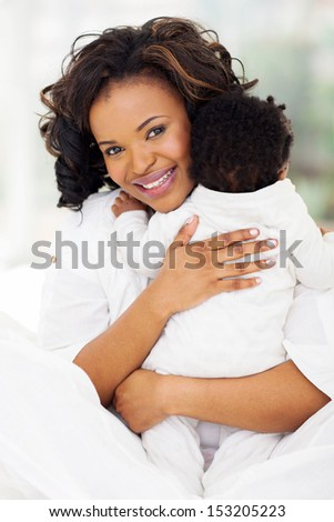 portrait of young mother holding her baby in her arms - stock photo