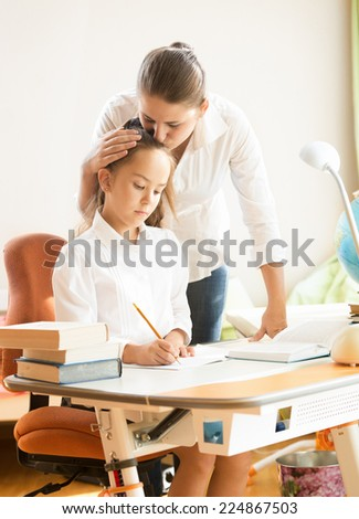 Portrait of young mother hugging and praising daughter while doing homework - stock photo