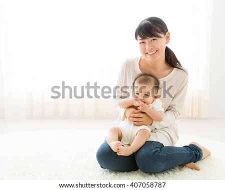 portrait of young mother hugging baby - stock photo