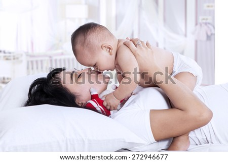 Portrait of young mother playing with small baby. shot at home - stock photo
