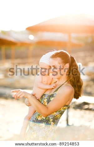 Portrait of young mother with baby on beach showing something by pointing in corner - stock photo