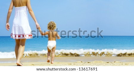 Portrait of young mother with her baby  having fun on the beach - stock photo