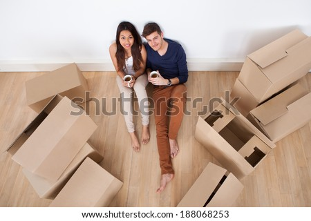 Portrait of young multiethnic couple holding coffee mugs while sitting on floor in new home - stock photo