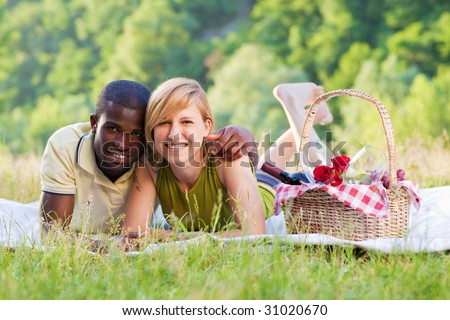 portrait of young multiethnic couple picnicking in park - stock photo