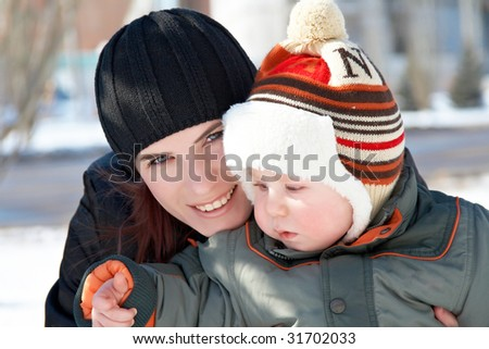 Portrait of young mum with the son in the winter on walk - stock photo