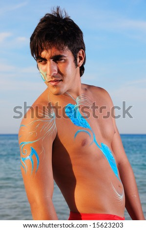 Portrait of young muscular hispanic model on the beach - stock photo