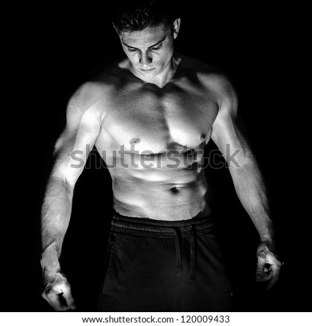 Portrait of young muscular man shirtless against black background - stock photo