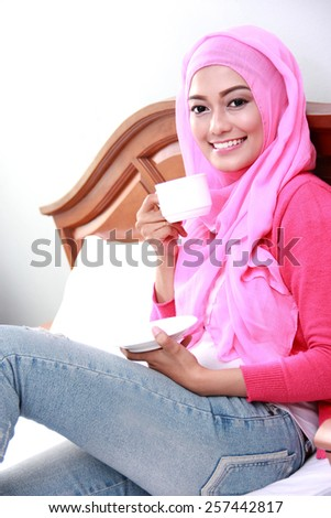 portrait of young muslim woman had a cup of tea for breakfast - stock photo