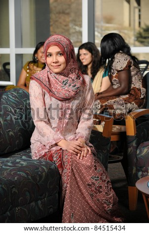 Portrait of young Muslim woman in traditional clothes with others in background - stock photo