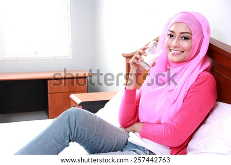 portrait of young muslim woman relax on bed and drinking a glass of milk for breakfast - stock photo