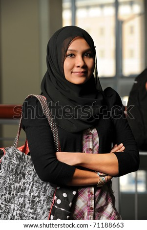 Portrait of young Muslim woman with arms crossed - stock photo