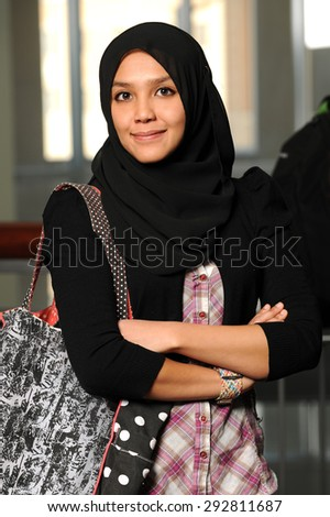 Portrait of young Muslim woman with arms crossed inside building - stock photo