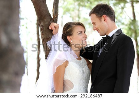 portrait of young newlywed couple staring each other lovingly with copy space - stock photo