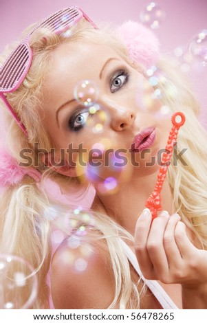 Portrait of young nice woman with soap bubbles on pink back - stock photo