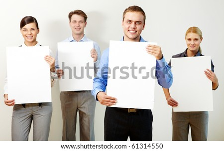 Portrait of young partners holding blank papers and looking at camera - stock photo