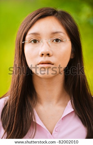 Portrait of young pensive attractive brunette woman wearing glasses at summer green park. - stock photo