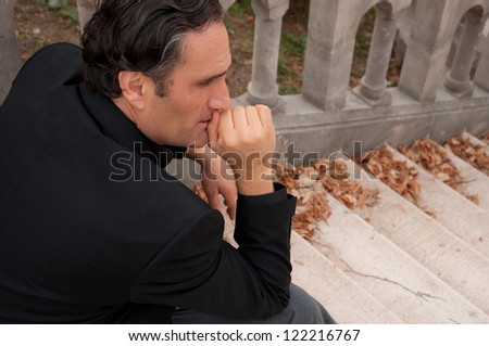 portrait of young pensive man,with black hair, seating on the stairs, holding his hand on the lips and thinking about his problems - stock photo
