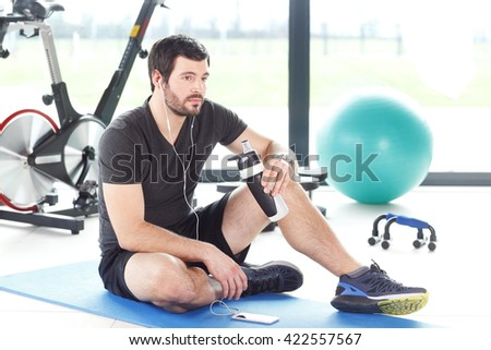 Portrait of young personal trainer relaxing after workout while listening music. - stock photo