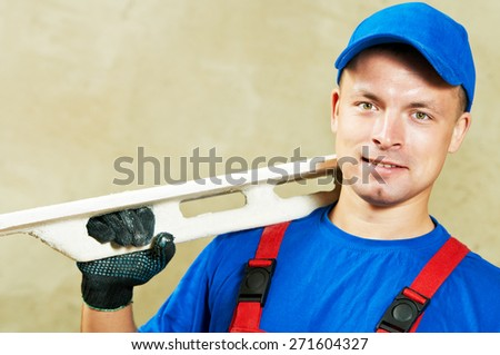 portrait of young plasterer with float over renovation wall backgroung - stock photo