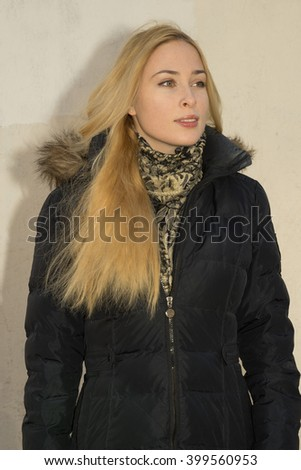 portrait of young positive blonde caucasian woman in black parka near the wall - stock photo
