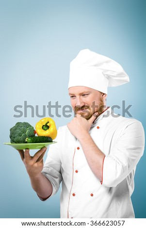 Portrait of young positive male chef in white uniform. Head-cook carefully looking at plate with fresh vegetables and standing against grey background - stock photo