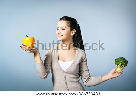 Portrait of young positive woman standing against grey background. Woman holding fresh broccoli with yellow paprika and looking at it. Concept for healthy food - stock photo