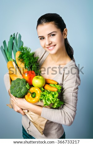 Portrait of young positive woman standing against grey background. Woman looking at camera and holding package with fresh vegetables and bread. Concept for healthy food - stock photo