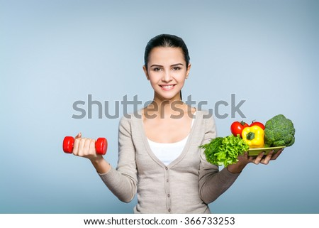 Portrait of young positive woman standing against grey background. Woman smiling and looking at camera. Woman holding in one hand dumbbell and in the other plate of fresh vegetables - stock photo