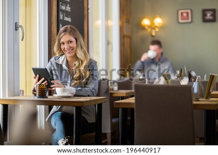 Portrait of young pregnant woman using digital tablet at table in coffeeshop - stock photo