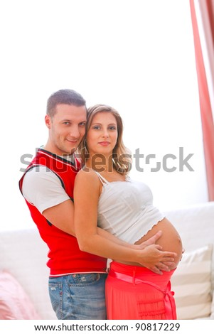 Portrait of young pregnant woman with husband hugging her tummy - stock photo