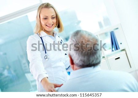 Portrait of young pretty assistant looking at mature clinician while interacting with him - stock photo