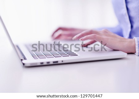 portrait of Young pretty business woman work on  notebook computer  in the bright modern office indoors - stock photo