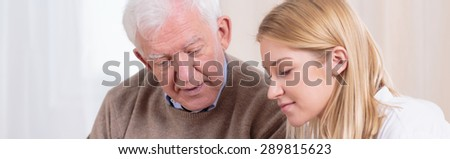Portrait of young pretty carer and elderly nice man - stock photo