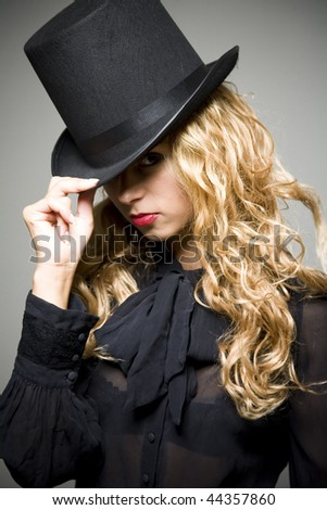 Portrait of young pretty girl in black with top hat in studio - stock photo