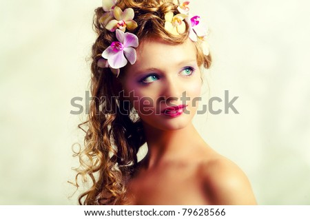 Portrait of young pretty girl with orchid flowers - stock photo