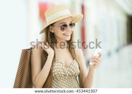 Portrait of young pretty happy smiling sexy woman wearing hat and sunglasses standing in shopping center, holding shopping bag and mobile phone, using smartphone app, looking at screen, messaging - stock photo