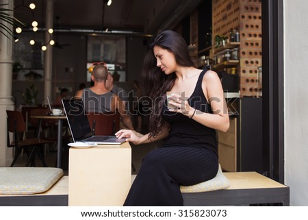 Portrait of young pretty latin woman working on her laptop computer while relaxing in modern cafe during coffee break, stylish female reading fashion news on net-book during breakfast in summer day - stock photo