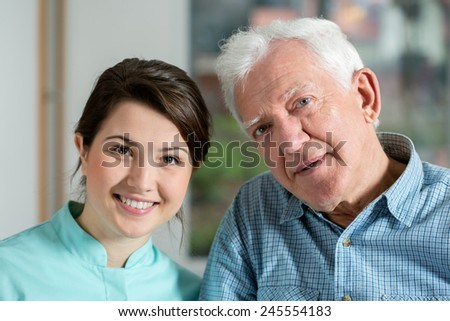 Portrait of young pretty nurse and her older happy patient - stock photo