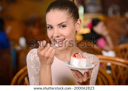 Portrait of young pretty smiling woman eating cake at shopping mall cafe - stock photo