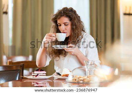 Portrait of young pretty smiling woman enjoying fruit cake and coffee at the coffee / cake shop - stock photo