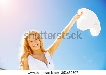 Portrait of young pretty woman cheering on sandy beach - stock photo