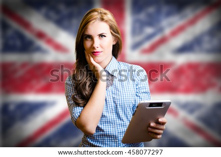 Portrait of young pretty woman holding tablet pc with the Great Britain flag on the background looking amazed - stock photo