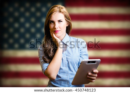 Portrait of young pretty woman holding tablet pc with the USA flag on the background looking amazed - stock photo